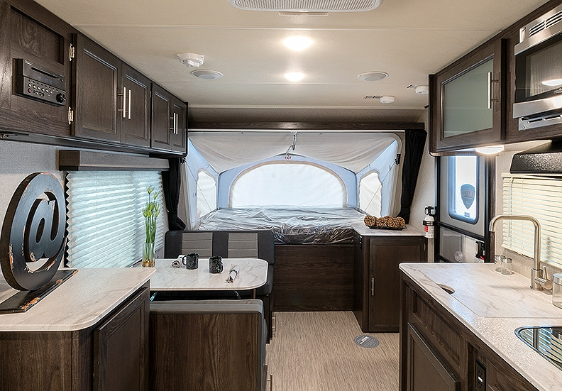 Inside the Kodiak Cub 1795 trailer with a view of the kitchen's light colored countertops and front tent extension.