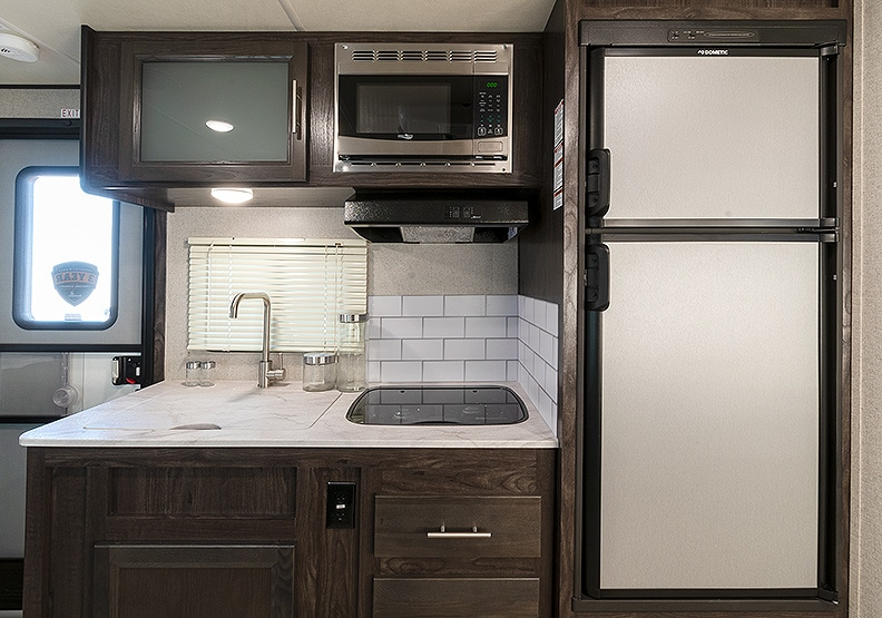 Kitchen with light colored counters, dark wood cabinets, microwave, sink and refrigerator.