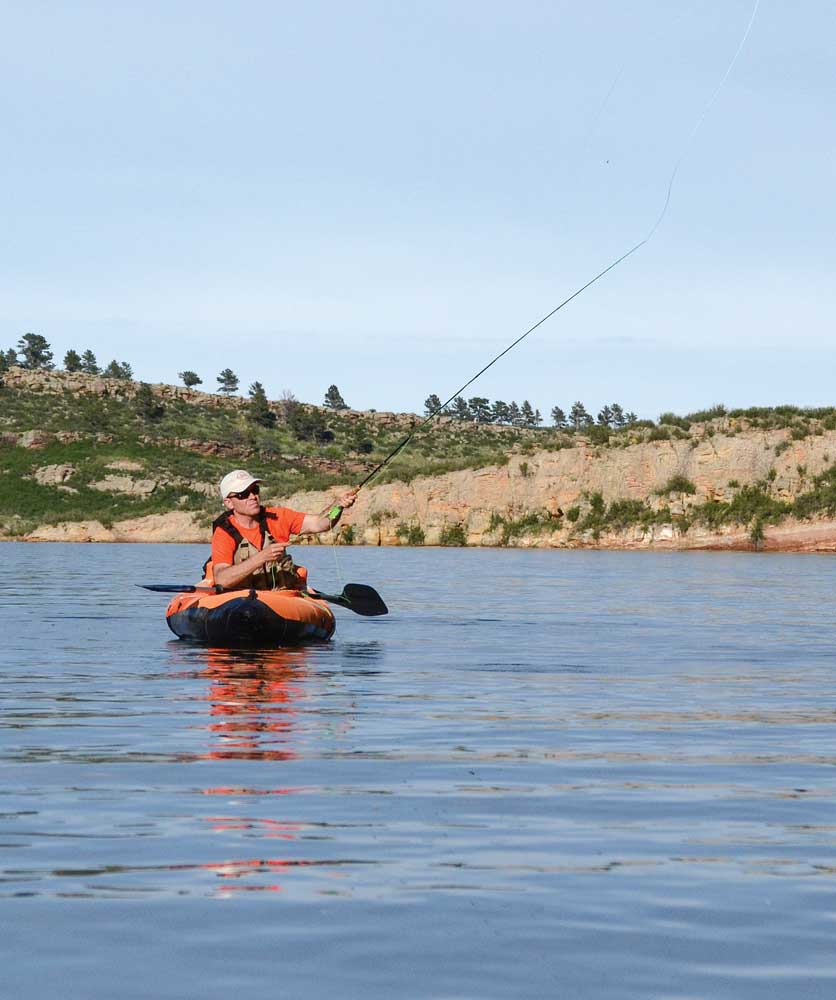 An angler casts from an inflatable kayak in a no-wake zone on Horsetooth Reservoir.