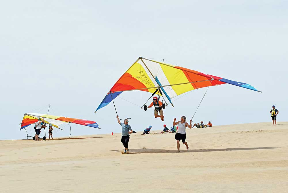 A hang-glider takes off on a flight with help from Kitty Hawk Kites instructors.