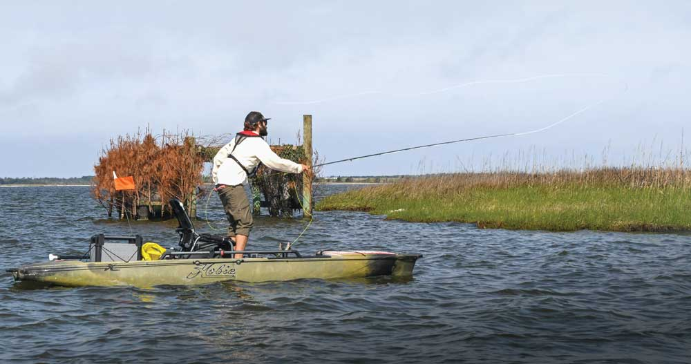 An angler casts for redfish near a permanent duck blind beside a salt marsh