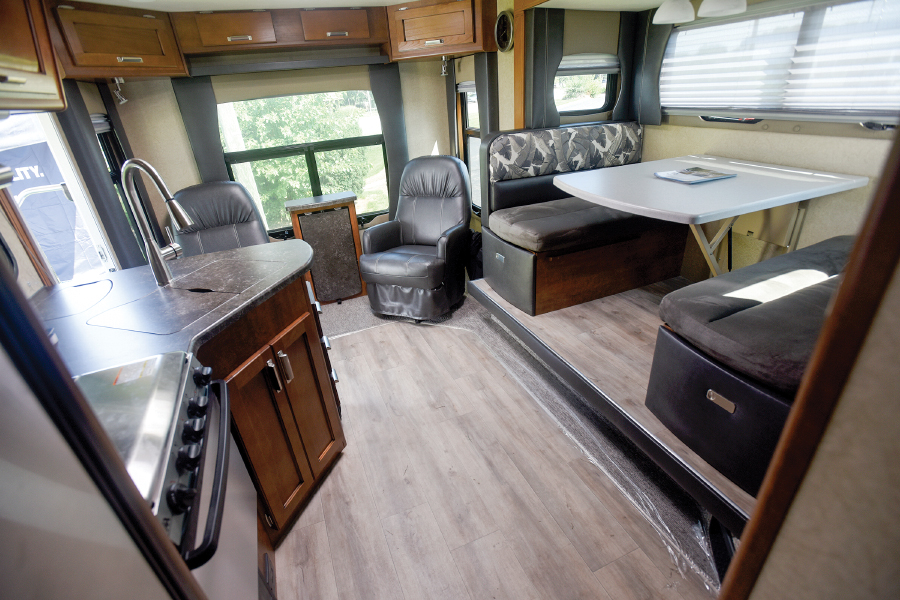 RV living area with table chairs and kitchen area