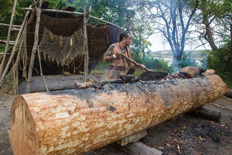 At the Wampanoag Homesite, a descendant works on a conoe the traditional way, by burning away the interior of a large white pine log.