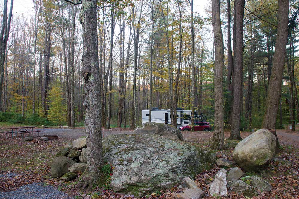 An RV in a campground with trees and boulders