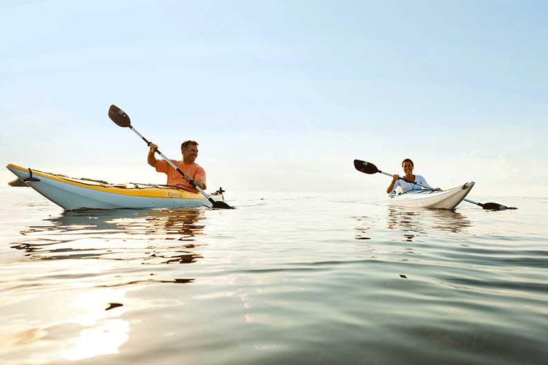 Two kayakers dipping their paddles in the Florida Keys