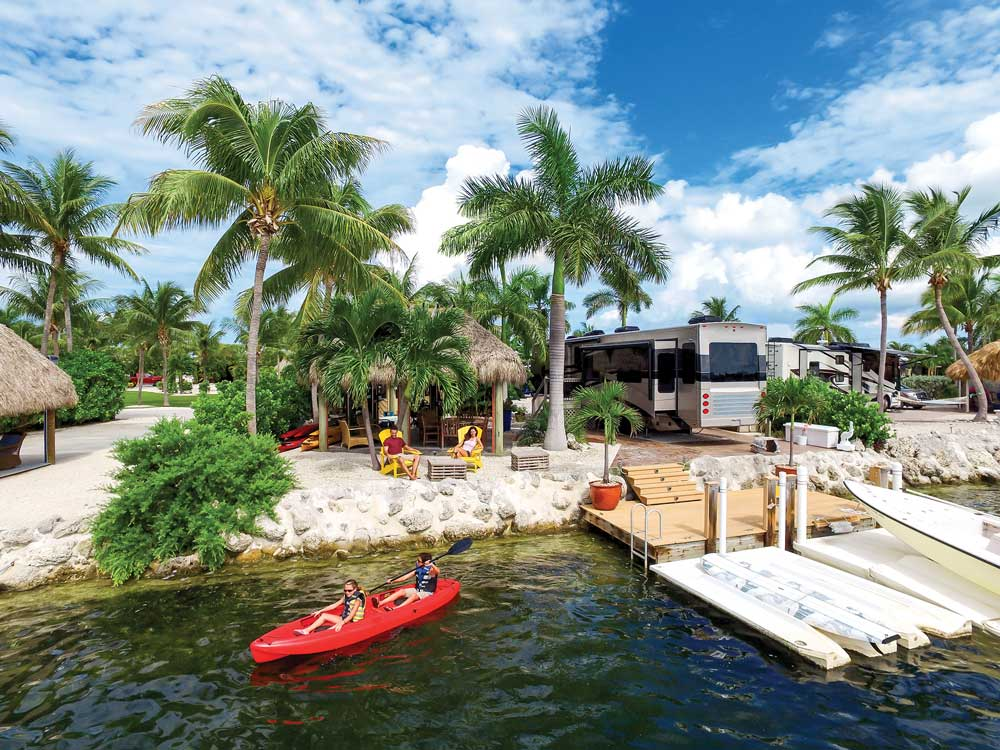 Beautiful dock in Lower Keys with palm trees and red kayak with people
