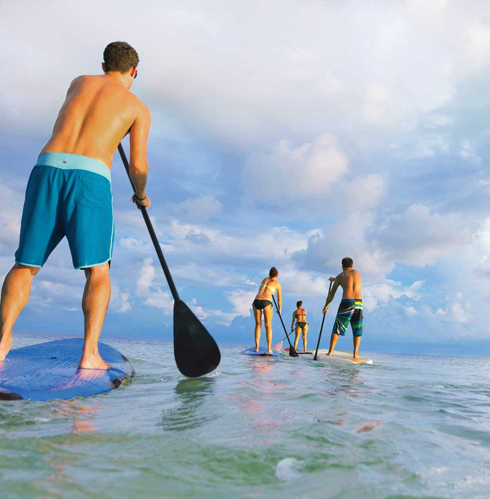 Two men and two women paddle boarding in Florida