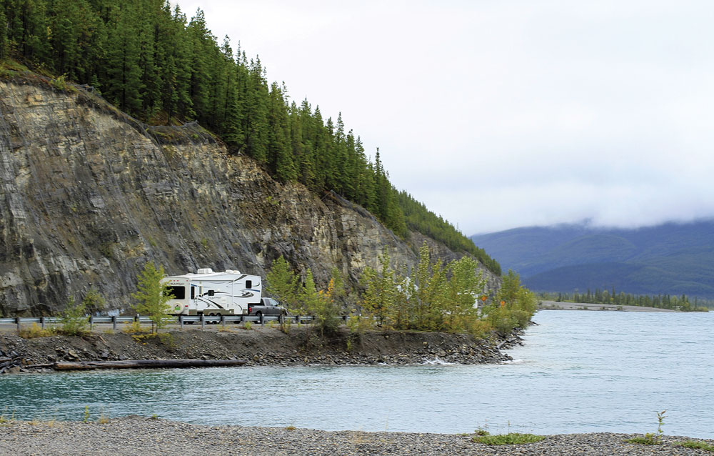 An RVer follows the shoreline of 7.5-mile-long Muncho Lake, a favorite stop for travelers on the Alaska Highway.