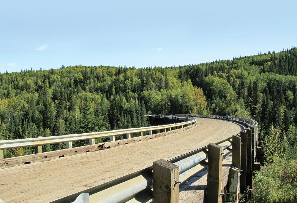 Curving 9 degrees along its 534-foot timber span, the Kiskatinaw Bridge is the only original Alaska Highway bridge still in use.