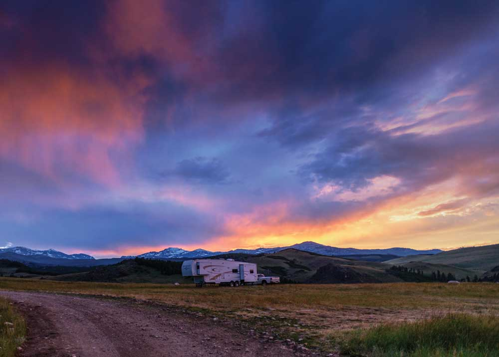 A fifth-wheel RV parked under stormy skies in high desert setting.