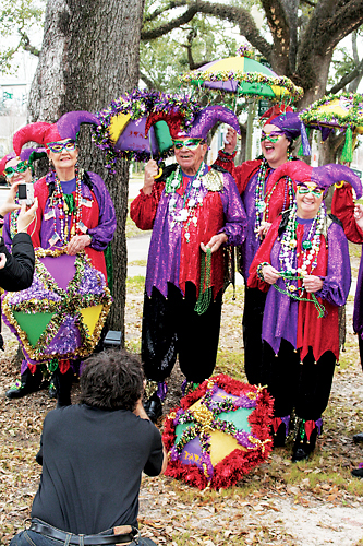 Four people wearing red and purple Mardi Gras costumes outside