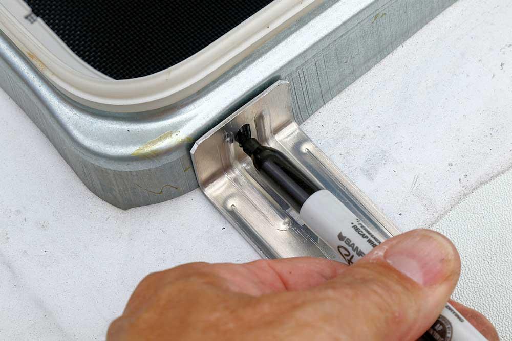 Technician marks location for instllation of bracket