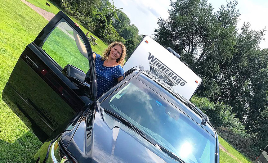 Stephanie Puglisi getting out of the SUV towing a Winnebago trailer