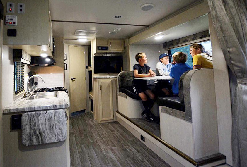 Family seated at dinette inside RV trailer