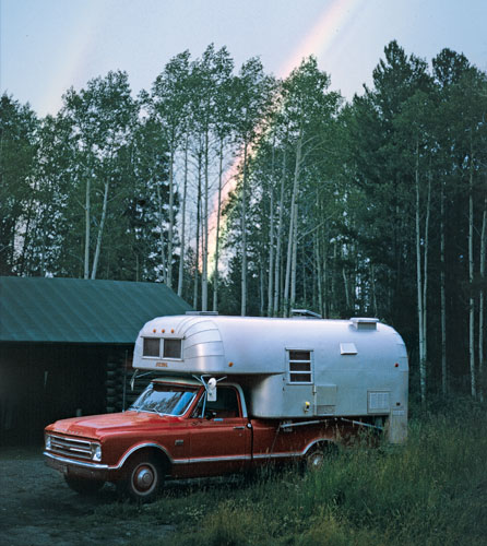 Red truck with silver trailer on top and rainbow behind tall trees