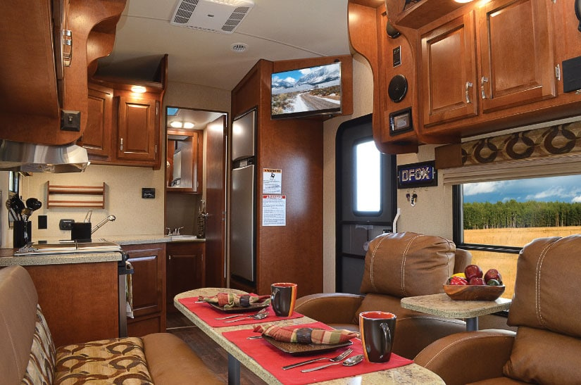 Nice RV living area with dining table and leather chairs