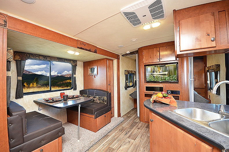 Warm brown cabinetry surrounds the booth dinette in a slideout.