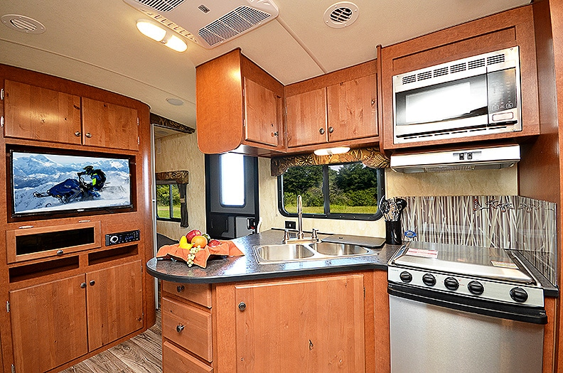 Dark colored L-shaped countertop with warm brown cabinets