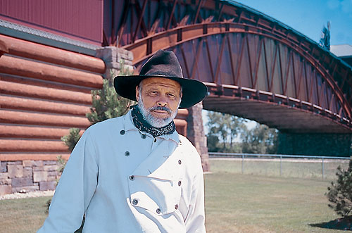 man with cowboy hat on posing in front of bridge