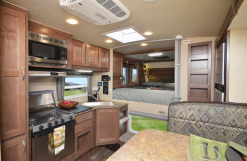 Interior of 990 camper with bed in background and kitchen in foreground.