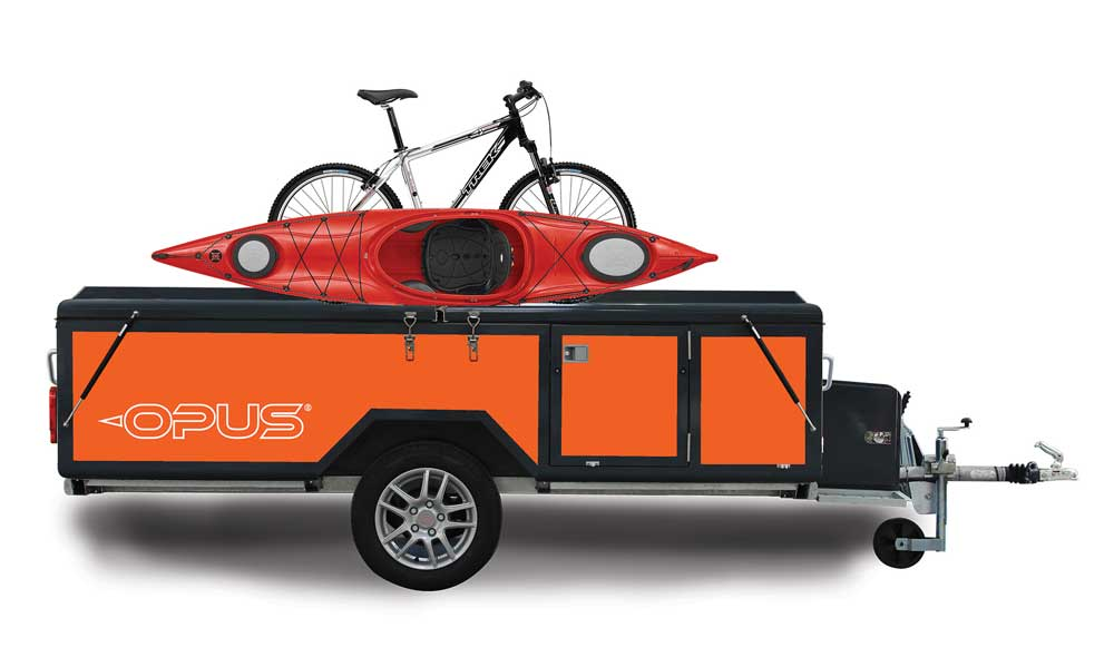 Kayak and bike on the cargo rack of a folding camping trailer with gear in the cargo basket