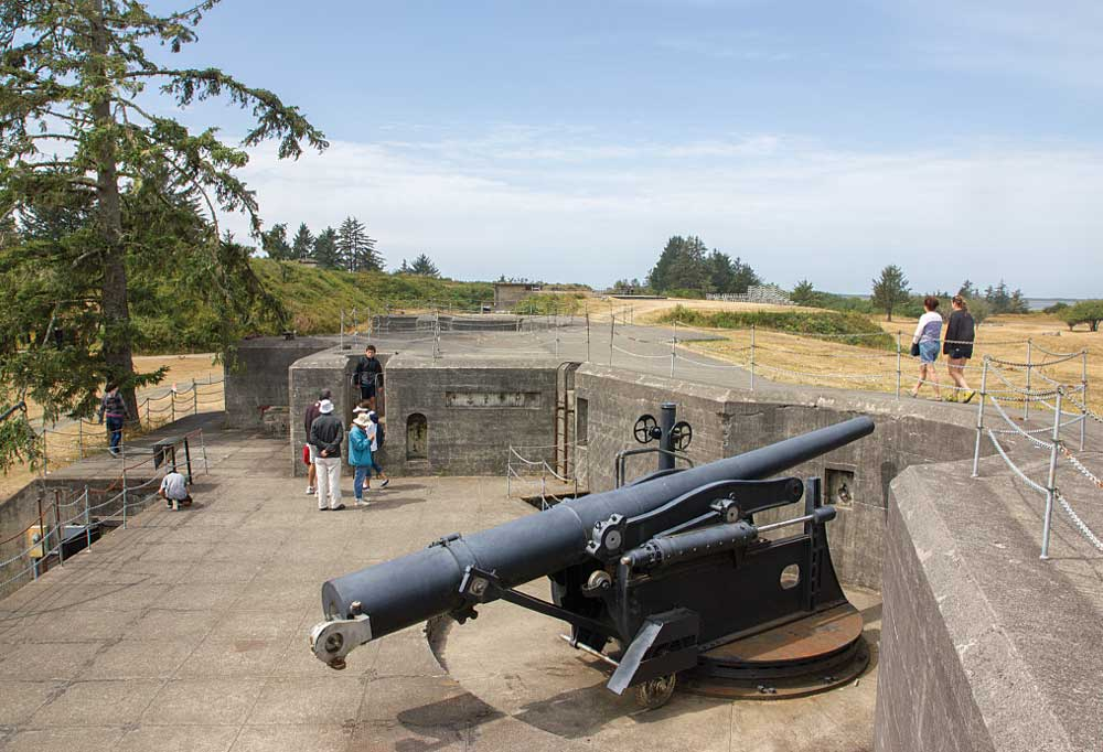 A huge cannon is in the foreground as visitors tour Battery Pratt in Fort Stevens State Park, Oregon