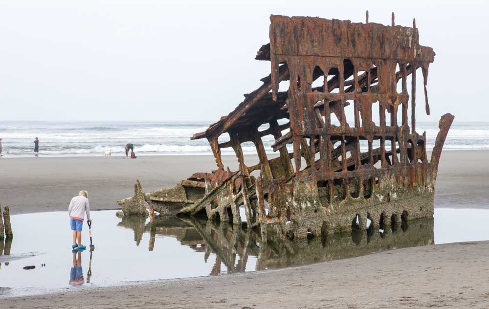 A boy and the wreckage of the Peter Iredale are reflected in the water at Fort Stevens State Park in Oregon.