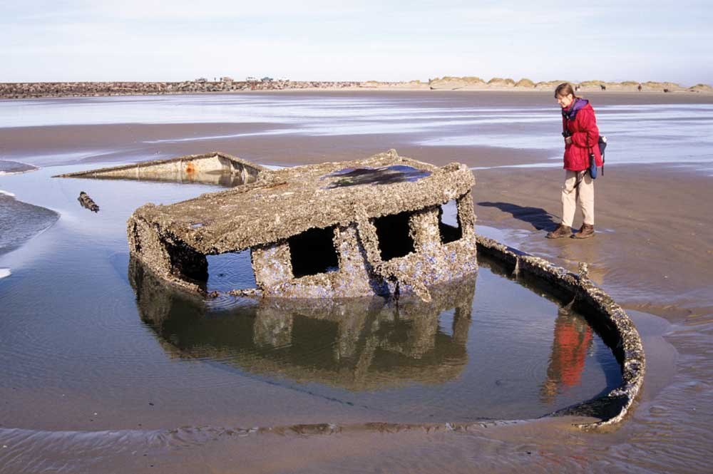 The author surveys the remains of a fishing vessel at South Beach State Park in Newport.