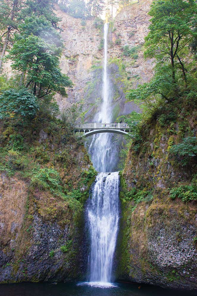 Visitors on the viewing bridge are dwarfed by Multnomah Falls in Oregon