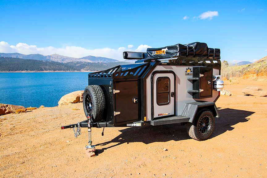 Expedition trailer on sand in front of blue water.
