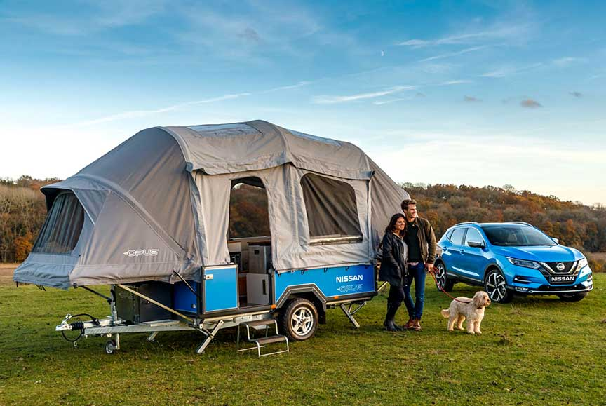 Couple in front of Opus camper dexter to blue Nissan SUV.