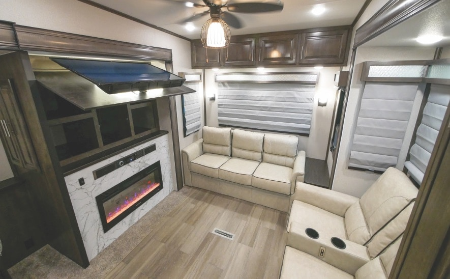 RV living area with electric fireplace inset in faux marble