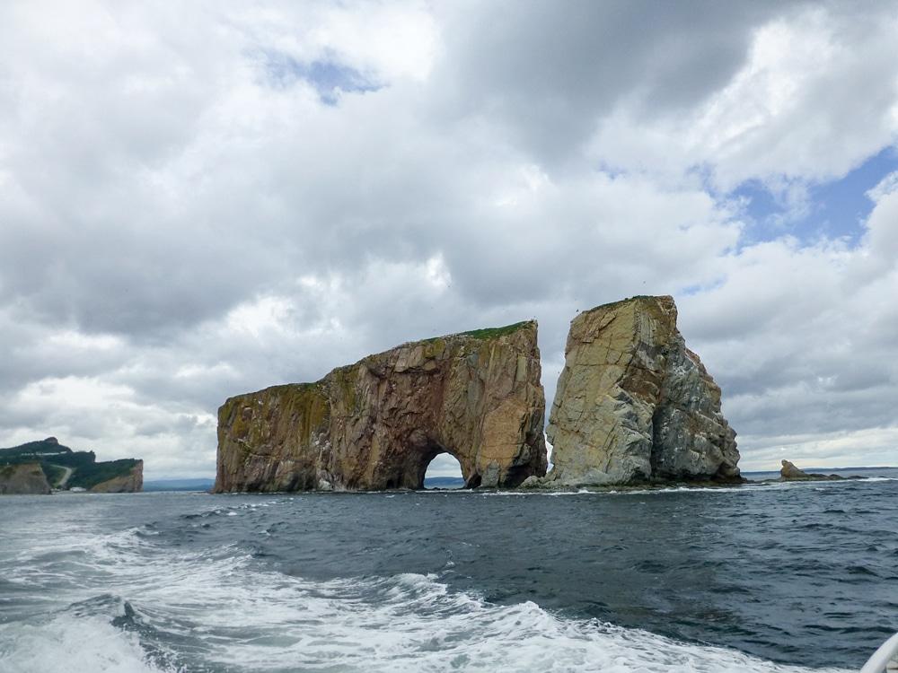 In the Percé harbor, a pierced limestone island rises 289 feet.