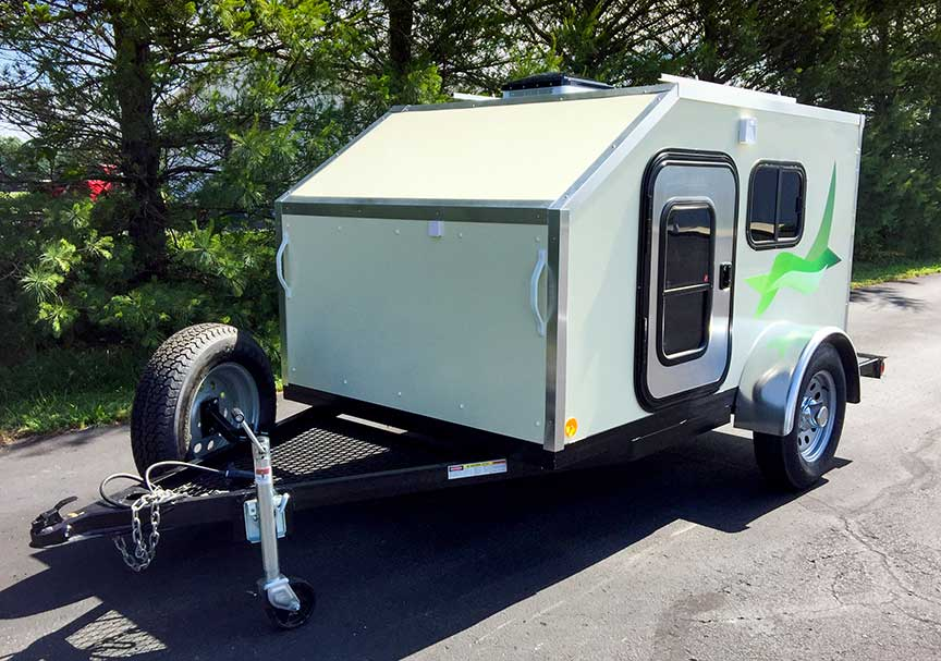 White PeeWee trailer with bright green graphic on side.