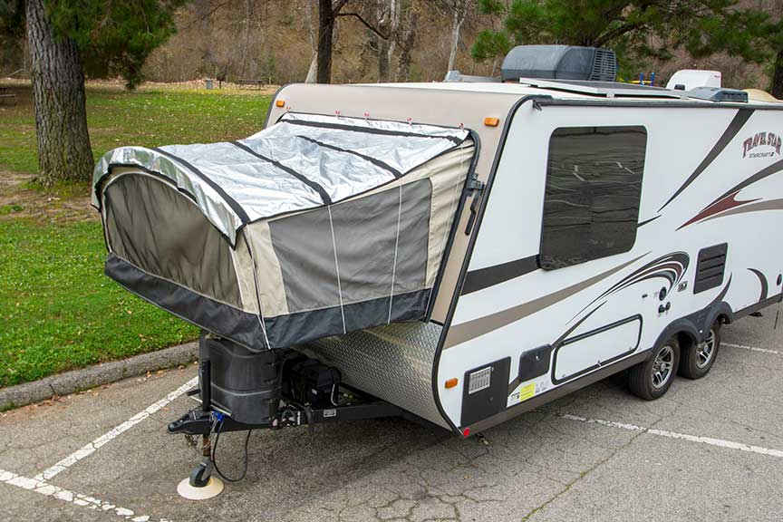White TravelStar hybrid trailer with PopupGizmos cover on front bunk-end at grassy park