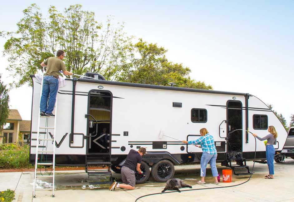 Four people washing a white travel trailer