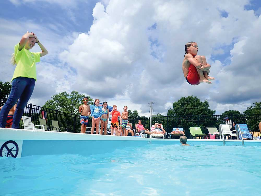 Woman wearing green shirt standing, looking at child doing cannonball in pool