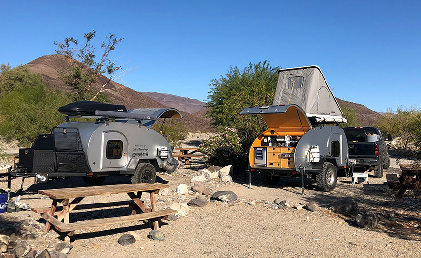 Two So-Cal Teardrops Kascade tiny trailers side by side in campsite