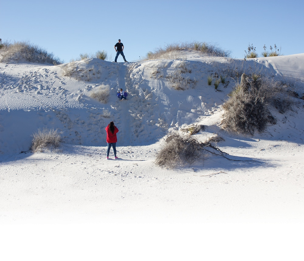 During the author's visit to White Sands National Monument, it was filled with families picnicking, teenagers playing rugby, children building sand castles, and people of all ages sliding down the dunes on sand sleds.