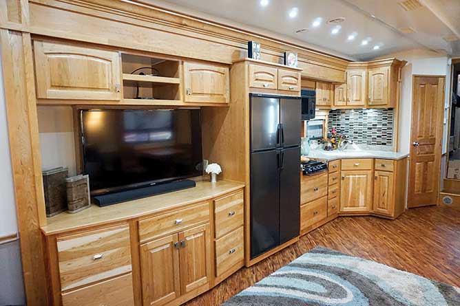 Wooden cabinets with tv and kitchen in large motorhome