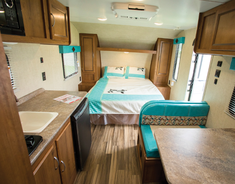RV living area with bed and kitchette