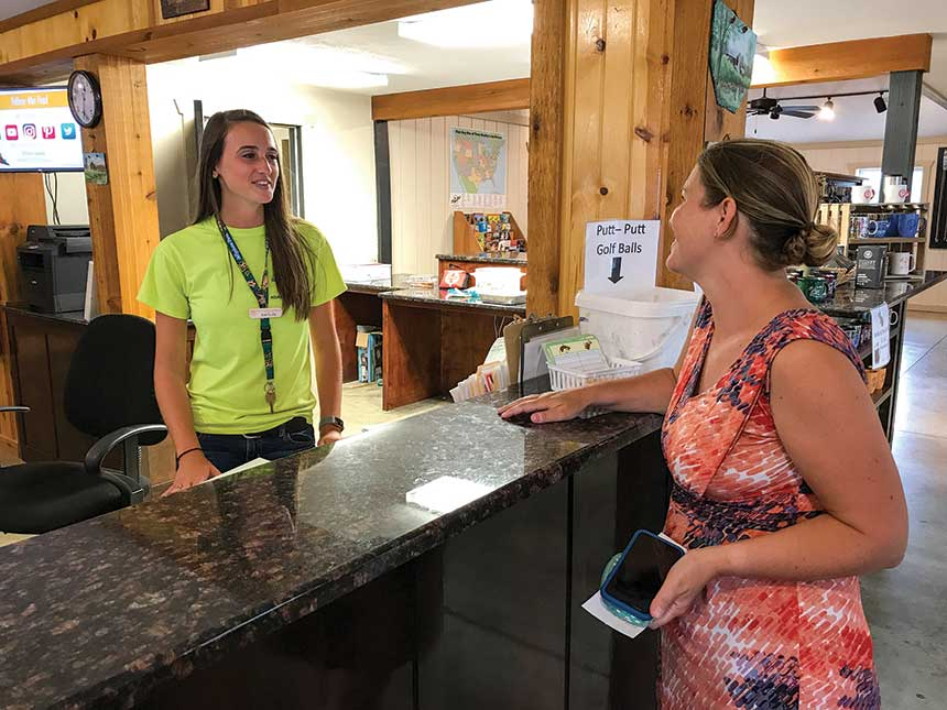 Woman wearing green shirt talking to woman behind counter