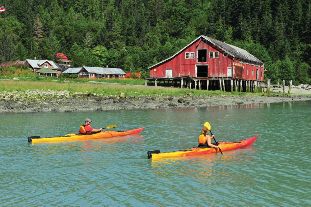 Paddling a sea kayaks past the Tallheo Cannery, one of the few remaining fishing canneries on British Columbia's Northwest coast.