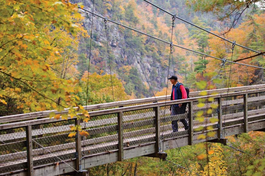 A hiker in Tallulah Gorge State Park crosses the 200-foot-long suspension bridge just above the gorge floor.