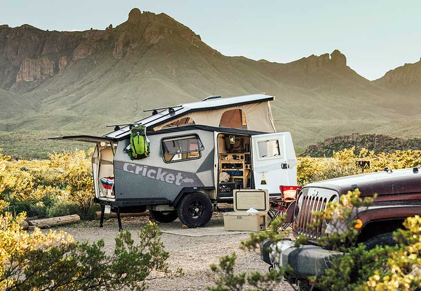 Cricket Overland trailer at rustic campsite with mountain ridge in background.