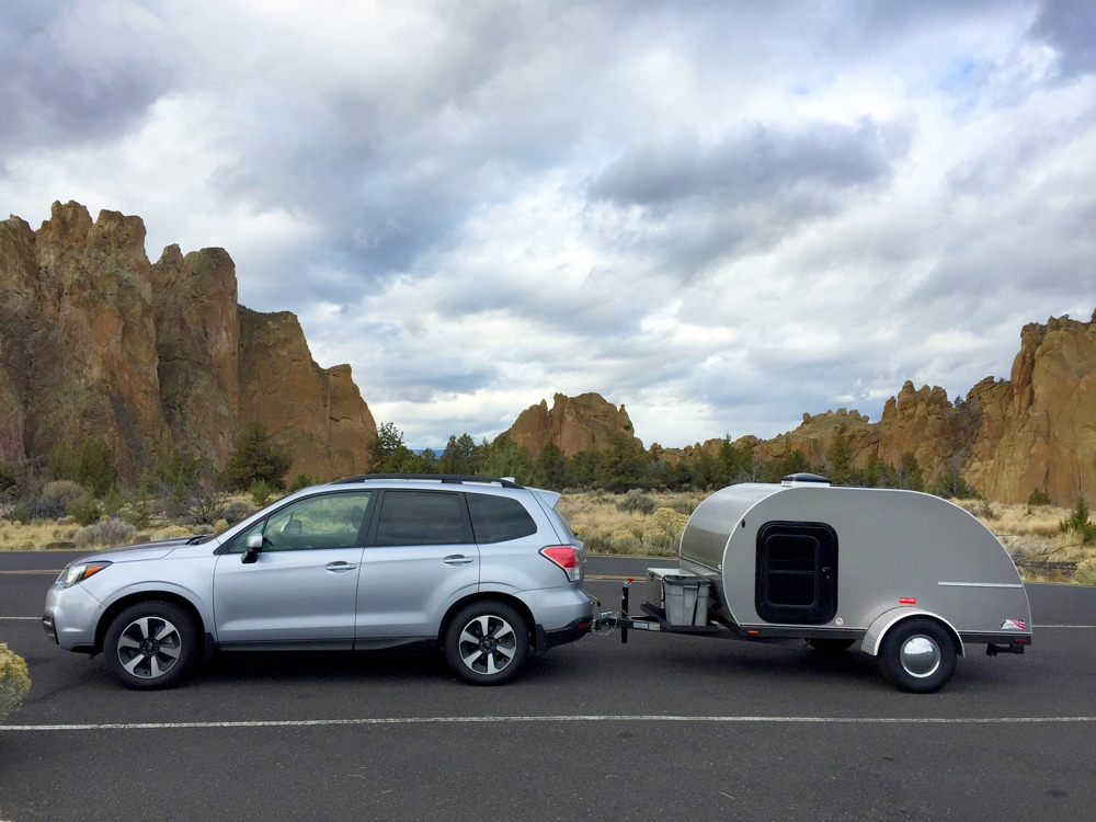 Light blue 4-door car pulling small silver travel trailer on desert road