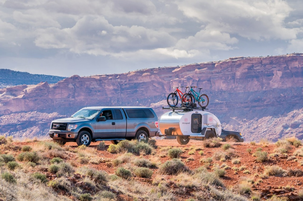 Truck pulling silver camper with bikes on top in desert