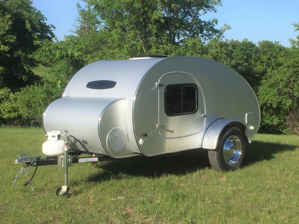 Tiny silver round travel camper parked on grass