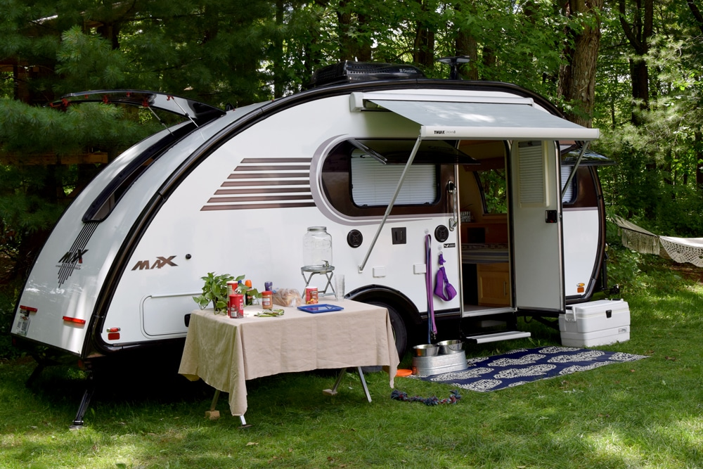 White Little Guy teardrop trailer with table in front on grass