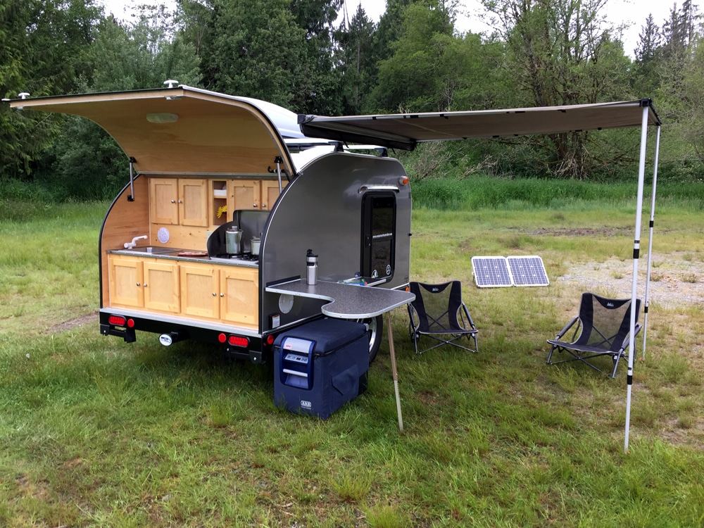 Silver teardrop camper with back door open and awning out